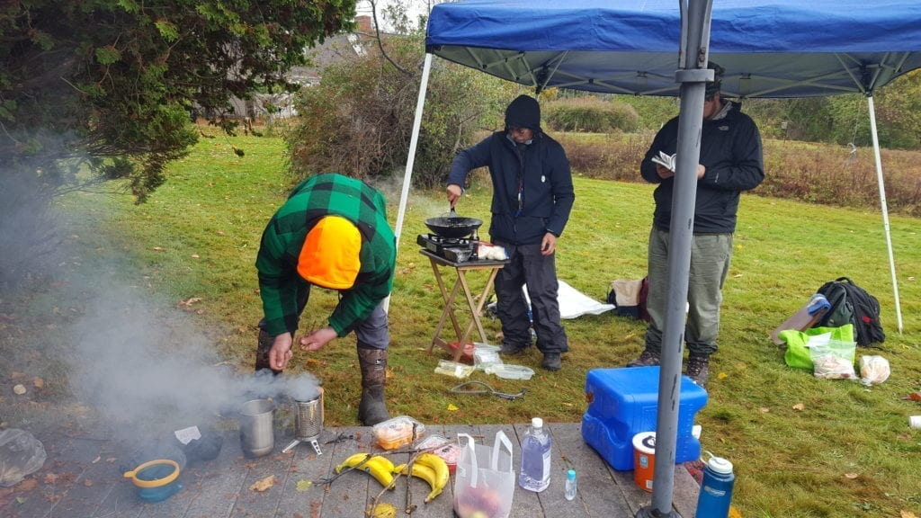 Kris cooks with his camping wok and Henry gets the BioLite stove going.